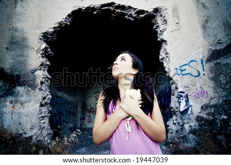 Young little girl with her teddy bear lost in a dirty place - stock photo