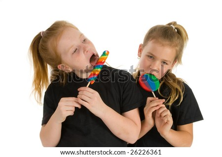 Young little girls with colored lollipops - stock photo