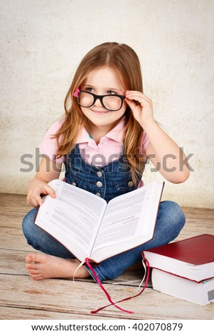 Young little nerd wearing glasses and reading a book - stock photo