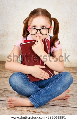 Young little nerd wearing glasses sitting on the floor and holding books - stock photo