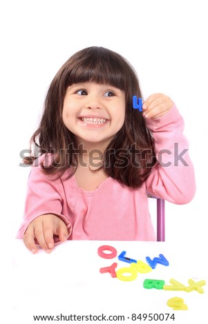 Young little preschool girl with funny expression playing with letters and holding up the number four showing her age - stock photo