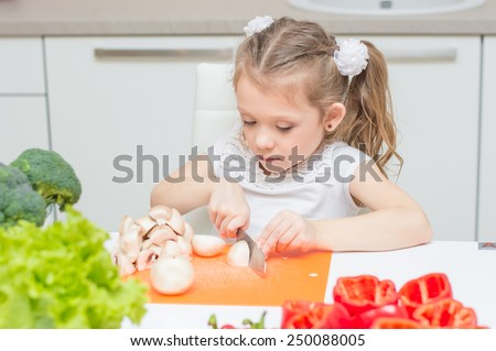 Young little pretty girl cuts the champignons with knife - stock photo
