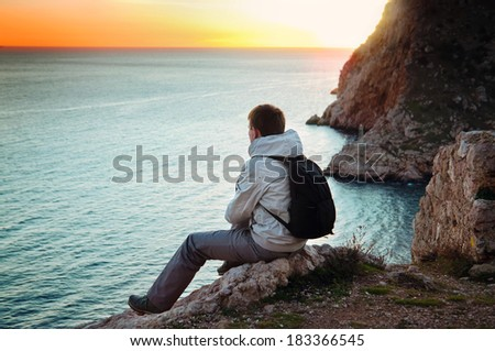 Young lone traveler sits on a hill and enjoys sea views - stock photo