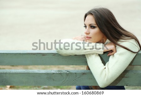 Young lonely woman on bench in park - stock photo