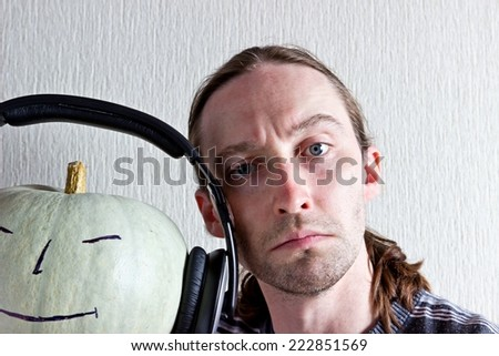 Young long hair man and pumpkin with smile and headphones. Halloween image