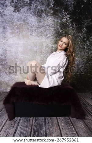 Young long-haired curly blonde woman on the sofa with a hairy blanket in front of an old dilapidated wall - stock photo