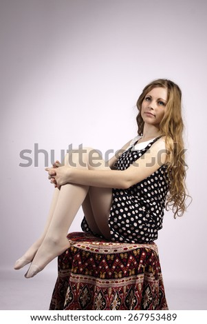 Young long-haired curly blonde woman sitting on chair, covered with mandala - stock photo