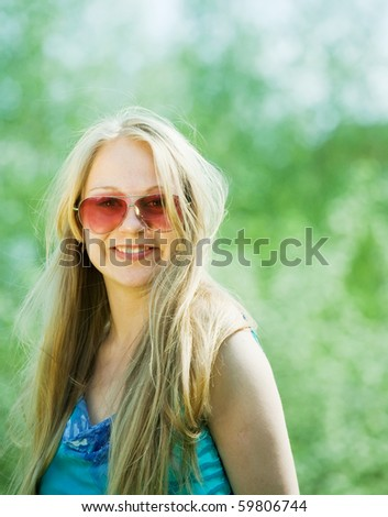young long-haired girl wearing sunglasses against nature - stock photo
