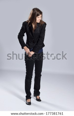 Young long-haired woman hiding in your pocket roll of dollars - stock photo