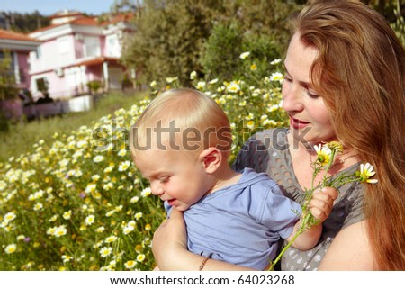 young looking grandmother with red hair holding her grandson in the field of daisies on the sunny summer day.
