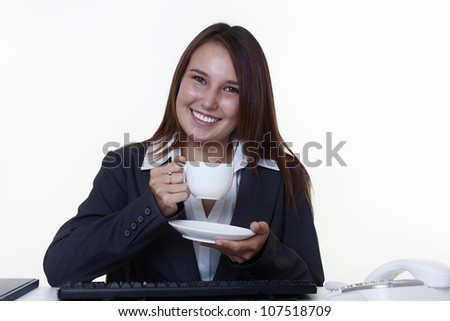 young looking woman drinking tea or coffee from a cup sitting at her desk at work - stock photo