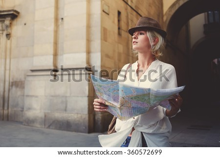 Young lost woman dressed in stylish clothes holding city map while standing in alley near vintage building,confused female tourist with location atlas in hands can not decide where to go while touring - stock photo