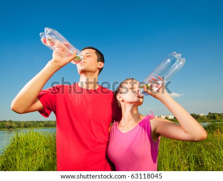 Young love Couple drink water under blue sky - stock photo