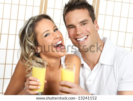 Young love couple drinking orange juce. Over white
