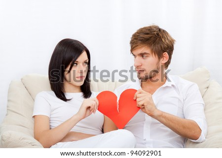 young love couple holding and break red valentine's heart together sitting on couch at home, unhappy looking to each other, valentine day no love concept - stock photo
