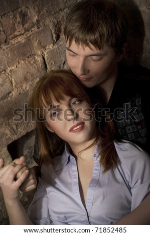 Young love couple on a background a brick wall - stock photo