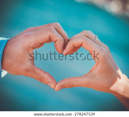 Young love couple put together hands in heart shape outdoor - stock photo