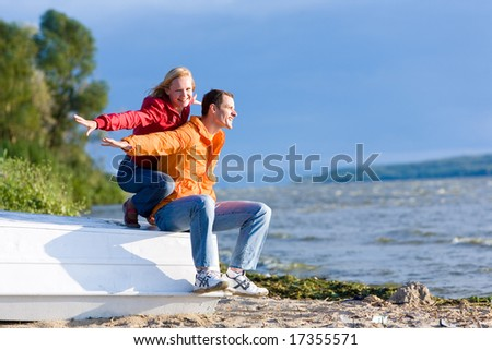 Young love Couple sit on boat on coast of river - stock photo