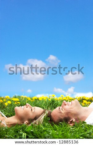 Young love couple sleeping on green grass - stock photo