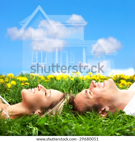 Young love couple smiling dreaming about a new home.  Real estate concept - stock photo