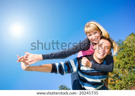 Young love couple smiling end fly under blue sky - stock photo