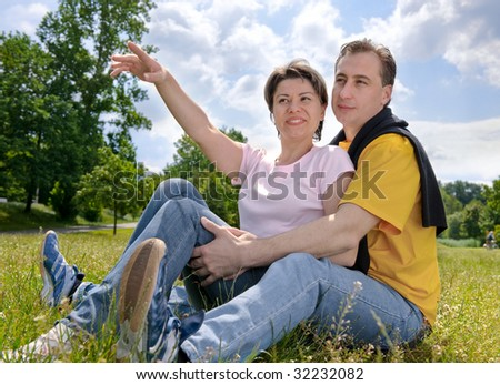 Young love couple smiling on the meadow - stock photo