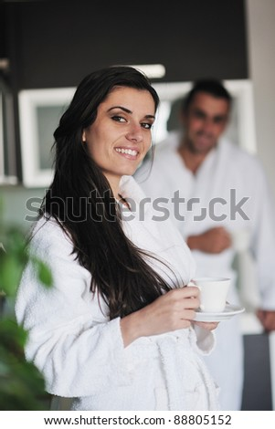 Young love couple taking fresh morning cup of coffee in the modern appartment - stock photo