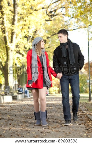 young love couple walking in romantic autumn park - stock photo