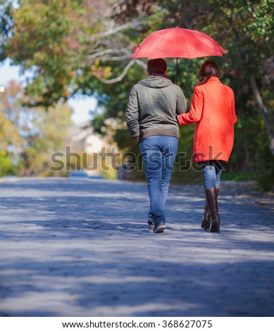 Young love couple with umbrella in spring day - stock photo