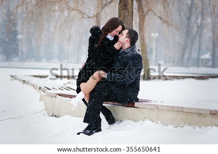 Young loved couple on winter snowy day