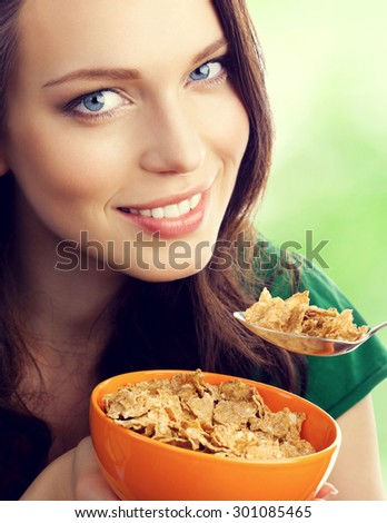 young lovely brunette woman eating muesli or cornflakes, outdoor - stock photo