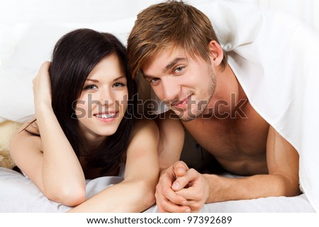 young lovely couple lying in a bed, happy smile looking at camera, cover under blanket - stock photo