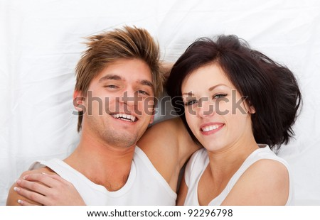 young lovely couple lying in a bed, happy smile looking at camera, top view. - stock photo