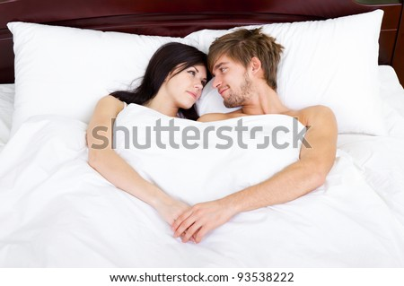 young lovely couple lying in a bed, happy smile love looking to each other, top above view, hold hands heart shape