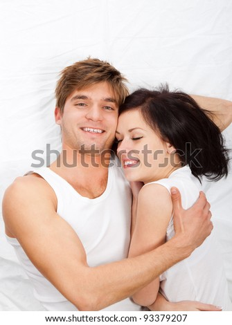 young lovely couple lying in a bed hug, happy smile looking at camera, girl closed eyes top view.