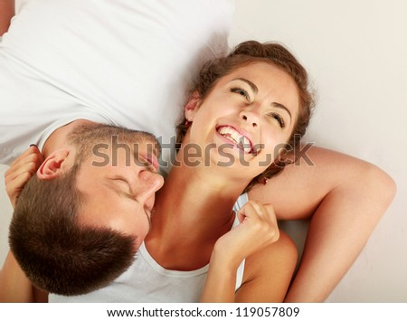 young lovely couple lying on the floor, isolated on white background
