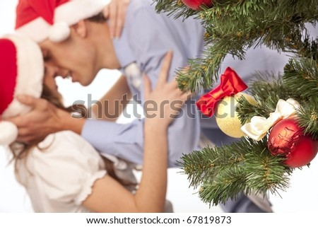 Young lovely couple near a Christmas tree with. (focus on christmas balls and fir tree ) - stock photo