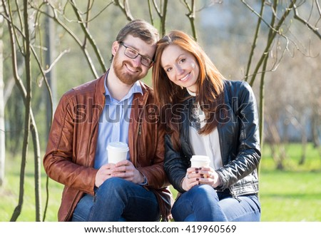 Young lovely couple with coffee sitting on bench in sunny day - stock photo