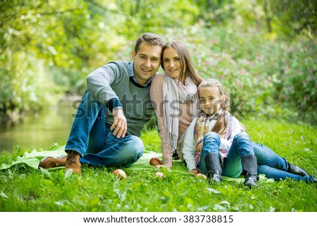 Young lovely family sitting on the green grass in the park and enjoying warm weather. Looking at the camera with sweet smiles. Happy healthy family on picnic.  - stock photo