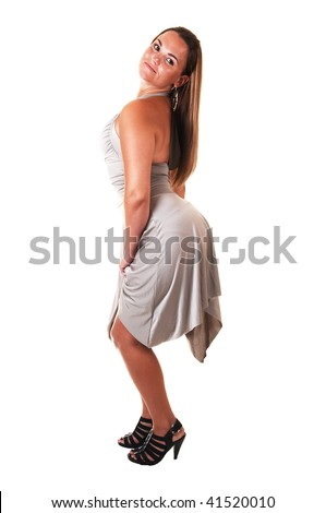 Young, lovely girl in a silver dress standing in the studio and shooing her but and legs, in high heels in the studio for white background.