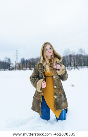 Young lovely girl in fur coat posing on winter snowy glade