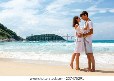 young lovely romantic couple on a beach looking affectionately at each other - stock photo