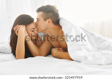 Young lovely tender couple enjoying morning lying in bed in their bedroom. Love and relationships concept. - stock photo