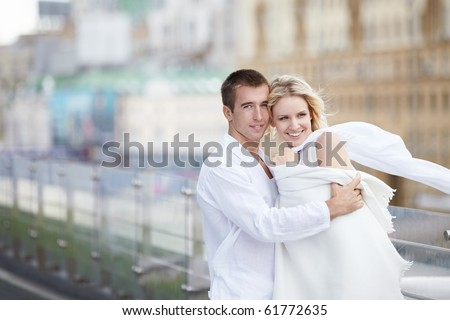 Young lovers in white on the roof - stock photo