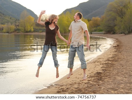 young lovers jumping for joy on beach at mountain lake - stock photo
