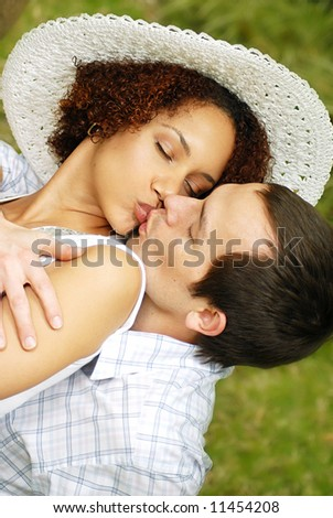 Young lovers kissing in the park on a lovely summer day