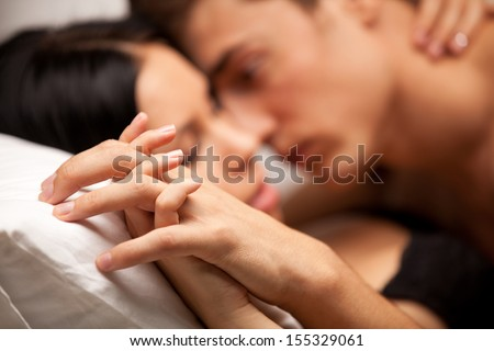 young lovers kissing on the couch. focused on hand