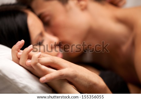 young lovers kissing on the couch. focused on hand - stock photo