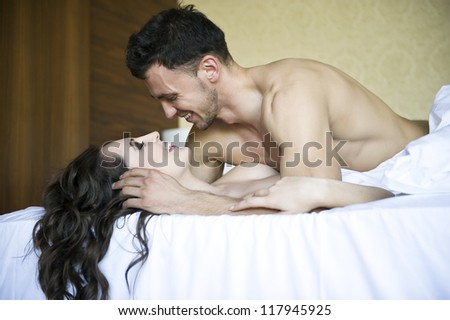 Young lovers lay in bed - stock photo
