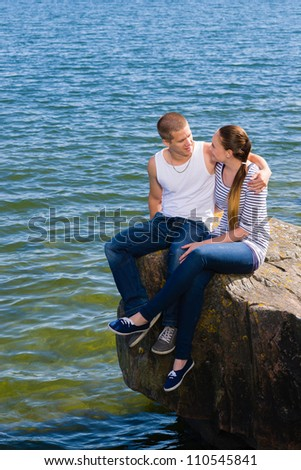 Young lovers looking and hugging each other on big rock